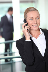 Smart business woman using a cell phone in office