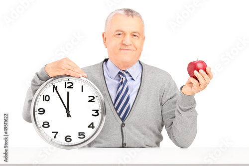 Smiling gentleman sitting and holding a wall clock and an apple