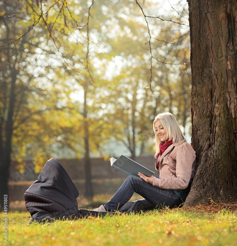 Young mother sitting in a park with her baby in a carrycot and r