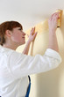 Woman putting up a wallpaper border