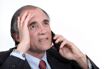 mature businessman on the phone trying to solve problem