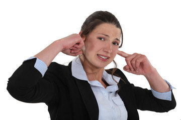 Businesswoman plugging her ears.