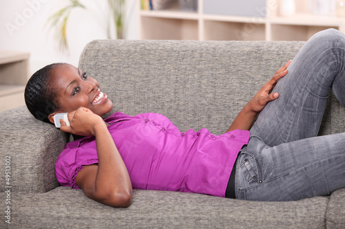 woman lying on settee with mobile phone