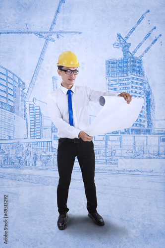 Engineer reviews blueprint plan