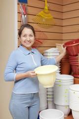 woman chooses plastic flower pot