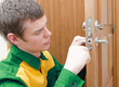 Young handyman in uniform changing door lock