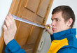 Young handyman in uniform working with measure tape