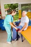 Mann bewegt Bein bei Physiotherapie