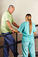 Senior neben Physiotherapeutin bei Bewegungstherapie