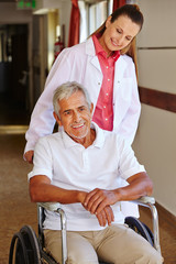 Mann im Rollstuhl mit Krankenpflegerin