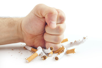 Human fist breaking cigarettes on white background