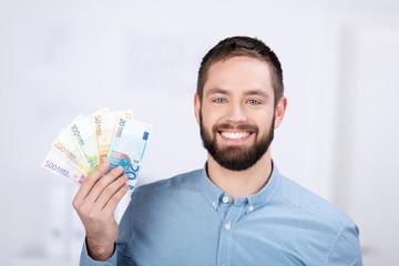 lächelnder mann hält geldscheine in der hand