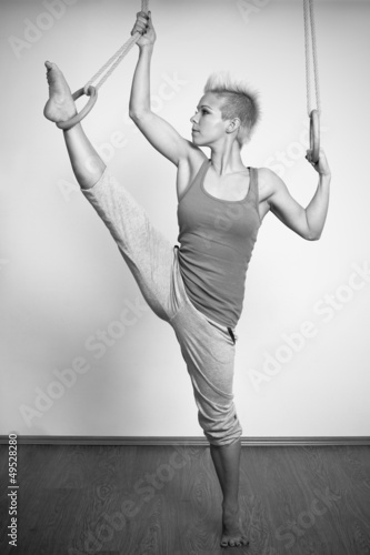 young woman gymnast competing on rings - black and white