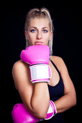 beautiful, fit woman wearing hot pink boxing gloves