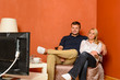 Young couple watching tv cuddling sitting armchair