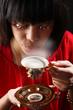 Junge Frau pustet auf heißen Kaffee und genießt