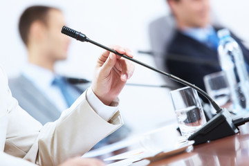 Hands of businessman holding microphone