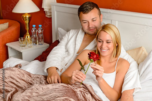 Loving couple celebrating romantic anniversary rose bed