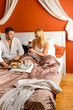 Loving couple sitting bed breakfast red rose