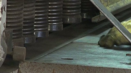 Men's hands are placed under the metal press