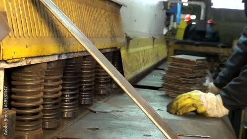 man puts a metal plate under the press
