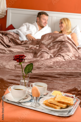 Happy couple lying bed romantic breakfast hotel