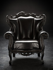 old black chair, upholstered in leather, isolated on a black bac