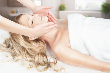 Blond girl is having relaxing facial massage in the spa salon.
