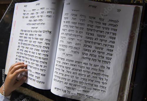 a boy's hand on a jewish bible
