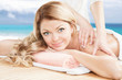 Blonde woman having a professional massage on the beach