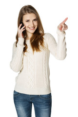 Happy woman talking on cell phone and pointing to the side