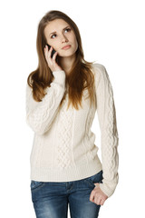 Pensive woman talking on cell phone looking up