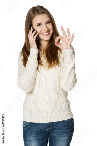 Happy woman talking on cell phone and showing OK sign