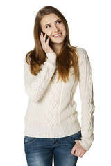 Smiling young woman talking on cell phone looking up