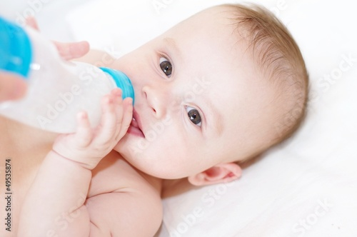 The five-months baby eats from a small bottle