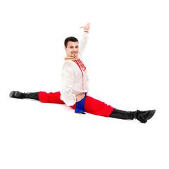 Smiling man wearing a folk ukrainian costume makes splits