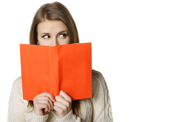 Woman peeking over edge of opened book, looking to side