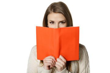 Woman peeking over the edge of the opened book