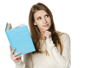 Thinking woman holding book and looking at copy space