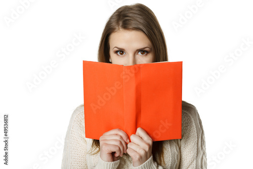 Woman peeking over the edge of the opened book