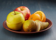 various chopped fruits plate on dark painted wooden table