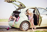 Two beautiful girls sitting in broken car and waiting for help