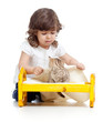 curly child girl playing with kitten as mother with baby