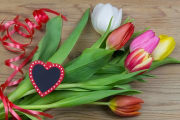 Tulpenstrauß auf Holz mit Geschenkband und Herz