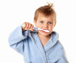 Little cute boy brushing his teeth on a white background