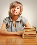 young woman sitting on the desk with pile of books