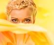 Beautiful young woman hiding behind big yellow flower