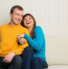 Happy couple sitting on sofa