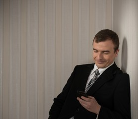 Handsome man in black suit with cell phone