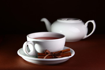 White cup and teapot on a brown background